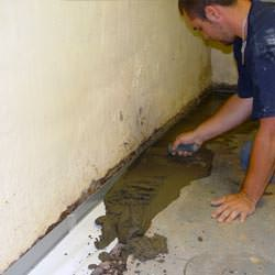 A basement waterproofer installing a perimeter drain system in Brownsburg